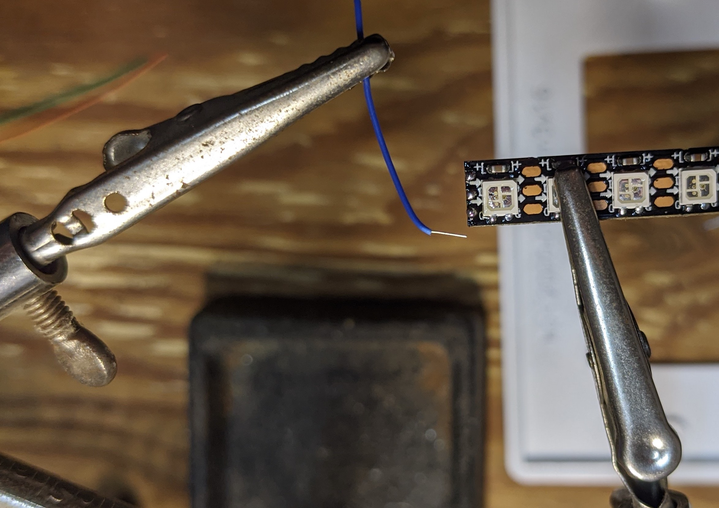 picture showing wire lined up with one solder pad on the LED tape